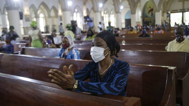A churchgoer wears a face mask and practises social-distancing to curb the spread of the coronavirus during a Sunday mass at the Holy Cross Cathedral in Lagos, Nigeria.