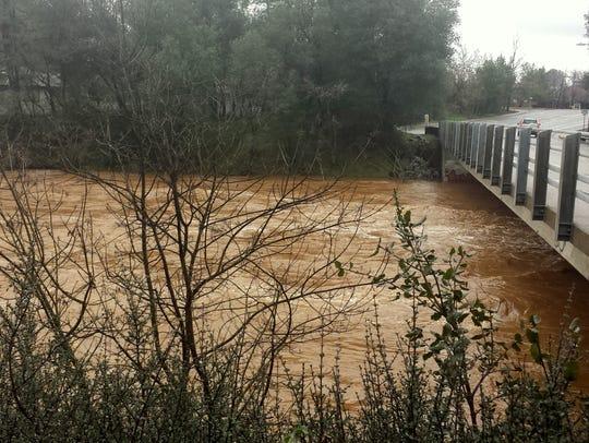 Churn Creek floods its banks under the bridge on Victor
