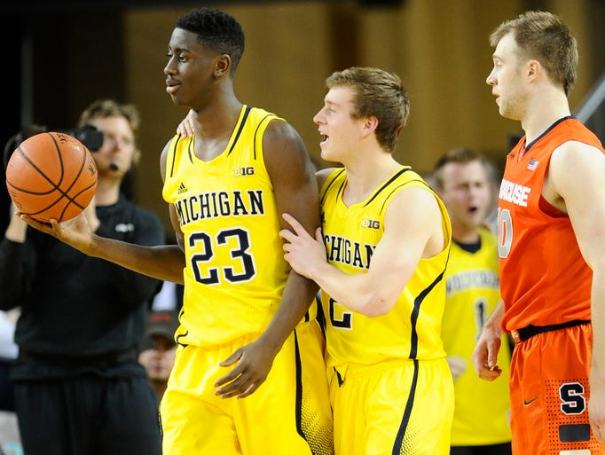 Michigan's Spike Albrecht (2) cheers on teammate Caris