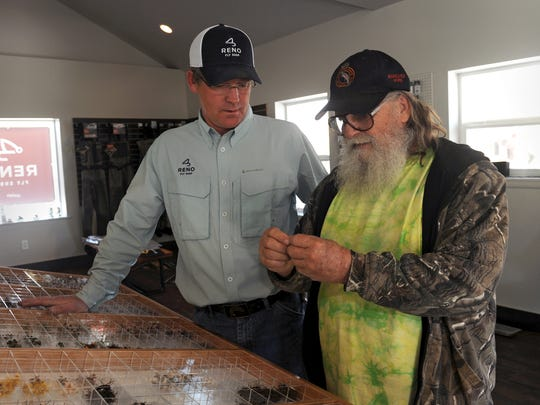 Reno Fly Shop co-owner Jim Litchfield, left, and with Pyramid Lake angler Kenny Dallimore look over some flies in shop that is set to open on Saturday April 19, 2014.