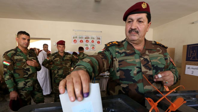 A member of the Kurdish Peshmerga force casts his ballot in special voting ahead of Iraq's election.