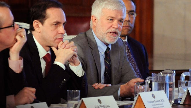 In this Dec. 17, 2014 file photo, New York environmental conservation commissioner Joseph Martens, right, explains the department's findings on hydraulic fracturing during a cabinet meeting at the Capitol in Albany.