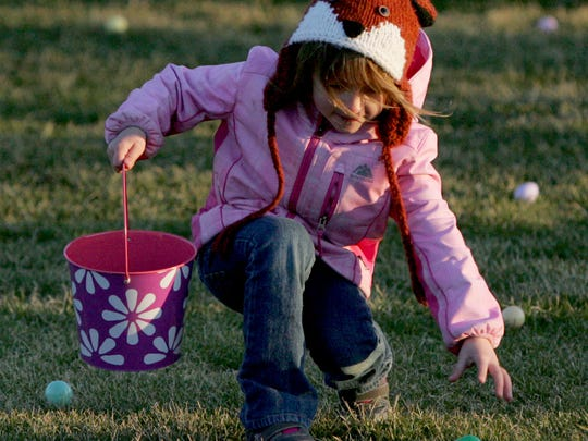 Kaelyn Wimmer scoops a candy-filled egg on the softball field of Village Park during a past Menomonee Falls Downtown Easter Egg Hunt.