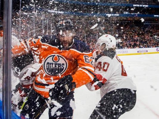 New Jersey Devils' Blake Coleman (40) checks Edmonton Oilers' Eric Gryba (62) during the first period of an NHL hockey game Friday, Nov. 3, 2017, in Edmonton, Alberta. (Jason Franson/The Canadian Press via AP)