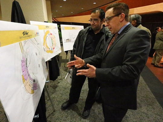 Ben Fyffe, right, assistant director for the city of El Paso Museums and Cultural Affairs Department, looks at plans for the Mexican-American Cultural Center with fellow department employee Nicholas Muñoz during its unveiling Monday night at the Abraham Chavez Theatre.