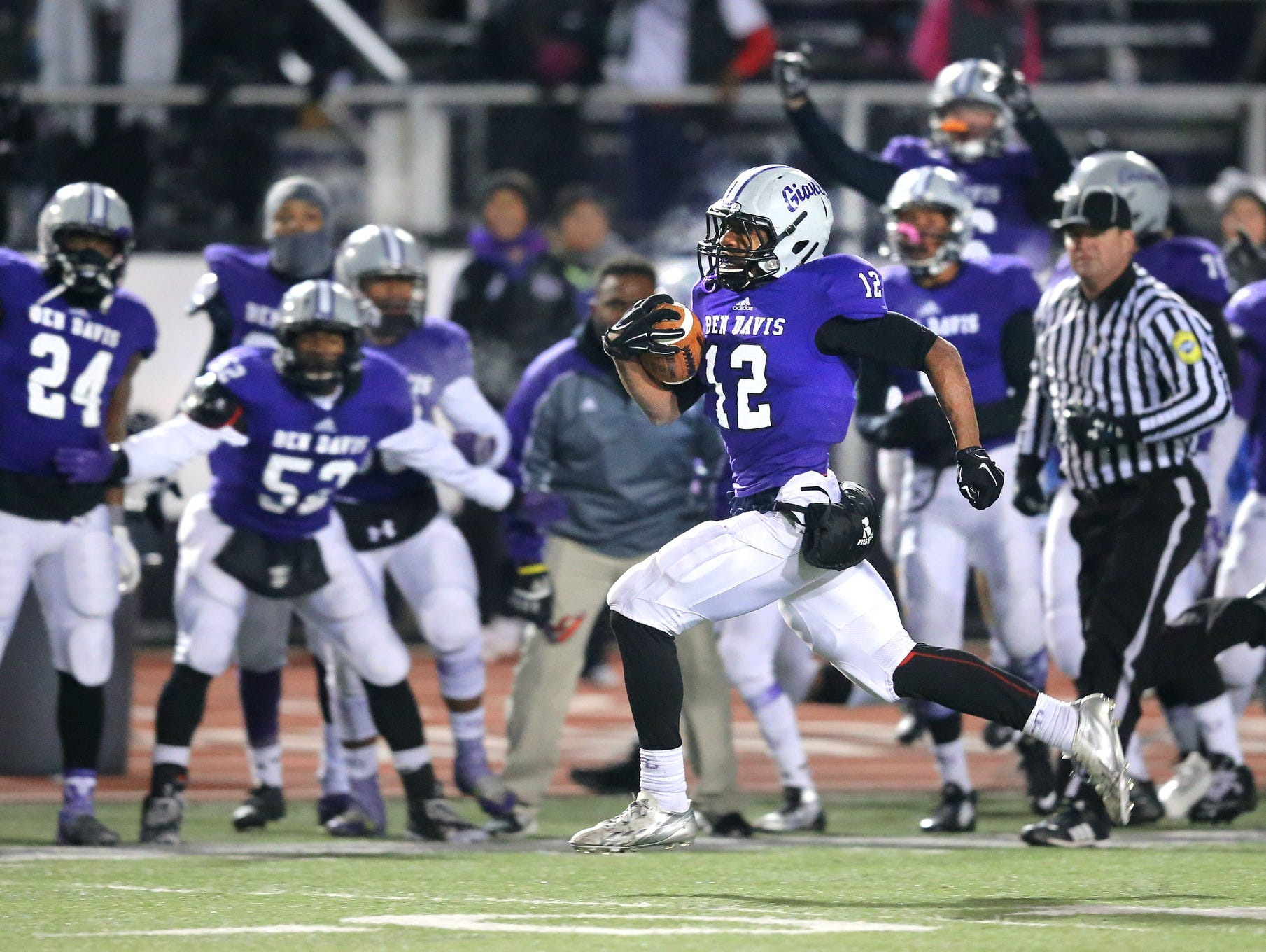 Ben Davis running back Chris Evans sprints down the sidelines for the winning touchdown as his team cheers him on in the final two minutes of the game. Ben Davis held on to beat Center Grove 49-45 in the IHSAA Semi-State game held at Ben Davis High School on Friday, Nov. 14, 2014.