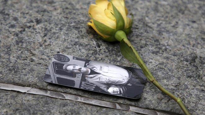FILE - In this May 30, 2019 file photo, a rose rests next to a photograph of New York City Fire Department Lt. Steven Reisman in the 9/11 Memorial Glade near the National September 11 Memorial & Museum. Reisman searched through the World Trade Center debris for remains, and then died in 2014 of brain cancer at age 54. When the names of nearly 3,000 Sept. 11 victims are read aloud Wednesday, Sept. 11, 2019, at the World Trade Center, a half-dozen stacks of stone will quietly salute an untold number of people who aren't on the list. (AP Photo/Seth Wenig, File)