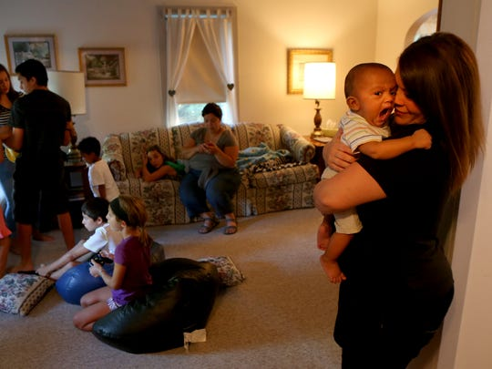 Rebecca Nerestant holds her son Gideon Nerestant, 6 months, as the rest of her family has a dance party and plays video games in the living room. Rebecca's family has grown from five to 10 after the death of five children's mother.