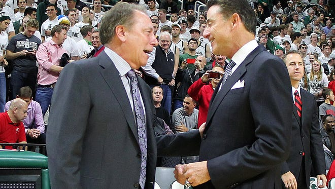 Michigan State basektball coach Tom Izzo, left, chats with Louisville coach Rick Pitino prior to their game at Breslin Center in December of 2015. Pitino is on administrative leave, about to be fired, his program caught up in the FBI probe that has all of college basketball on edge.