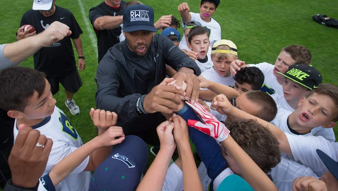 Seattle Seahawks quarterback Russell Wilson huddles up with young football players during a football camp for children aged 8-17, in Burnaby, British Columbia, on Friday July 10, 2015. The Russell Wilson Passing Academy is being hosted by the NFL quarterback in five U.S. cities in addition to the Canadian stop in Burnaby.