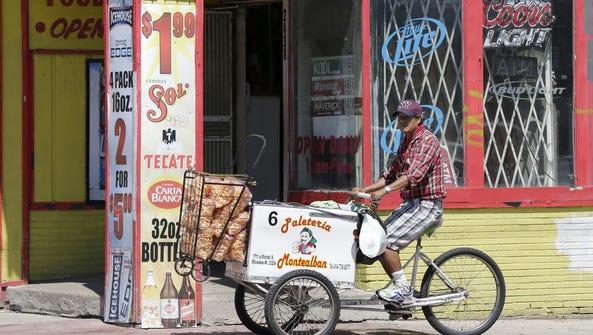 Rodolfo Lopez rides his Paleteria Montealban food cart