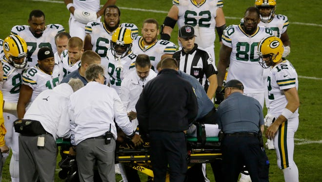 Teammates gather around Green Bay Packers wide receiver Davante Adams as he is taken from the field on a stretcher after being drilled by Chicago Bears inside linebacker Danny Trevathan  during the third  quarter at Lambeau Field.