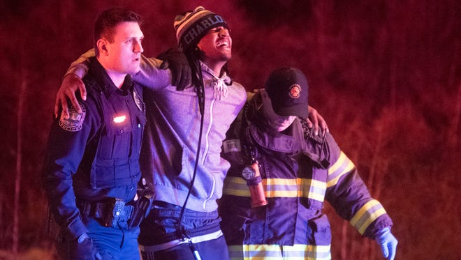 A possible shooting victim is helped to a waiting ambulance after a reported shooting at 6129 Western Ave. on Sunday, January 28, 2018.