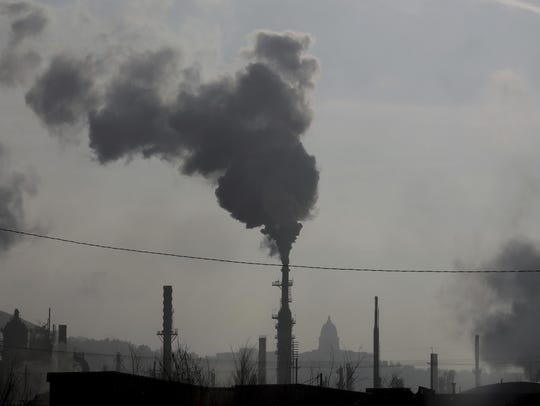 In this Dec. 10, 2018 photo, smokestacks near an oil