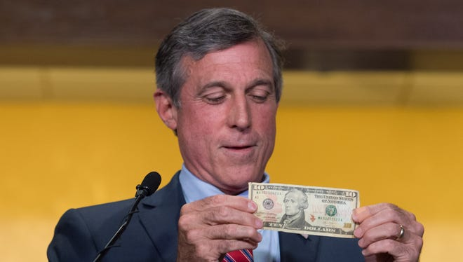 Gov. John Carney shows the $10 bill that he will use to bet on the Philadelphia Phillies vs. Chicago Cubs game tonight during a press conference before Delaware's single-game sports betting begins at Dover Downs Hotel & Casino in Dover.