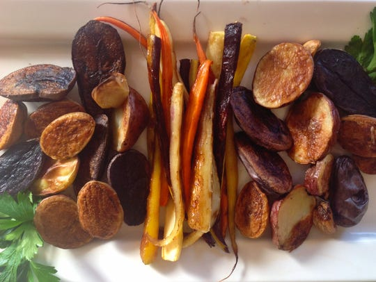 Roasted new potatoes and carrots are colorful sides.