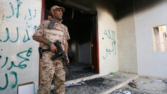 A Libyan military guard keeps watch in front of one of the U.S. Consulate's burned-out buildings on Sept. 14, 2012.