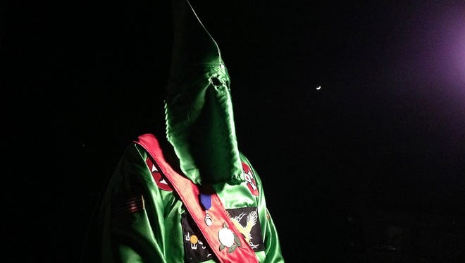 """In this photo taken Dec. 2, a robed and masked Ku Klux Klansmen stands on a muddy dirt road during an interview near Pelham. The KKK and other white extremist groups don't like being called """"white supremacists,"""" a phrase that dates to the earliest days of white racist movements in the United States."""