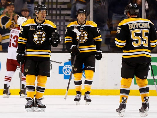 Boston Bruins' Jarome Iginla, left, goes to congratulate teammate Johnny Boychuk (55) after Iginla's goal against the Phoenix Coyotes as Milan Lucic looks on during the first period of an NHL hockey game in Boston Thursday, March 13, 2014. (AP Photo/Winslow Townson)
