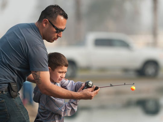 Chris Gonzalez, left, helps his son Jake Gonzalez, 6, cast his line during the Visalia Parks and Recreation's annual fishing derby at Plaza Park on Saturday, January 10, 2015.