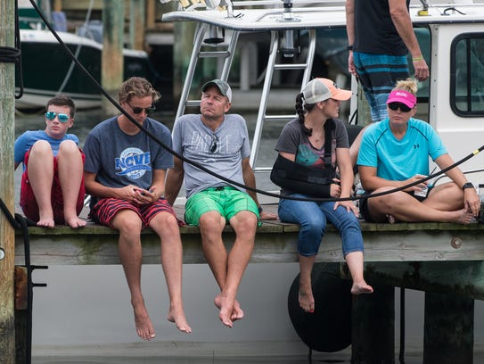 Spectators sit on a dock awaiting the arrival of incoming