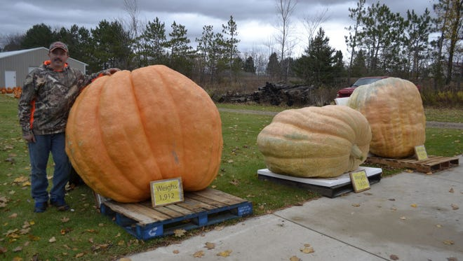 Tracy Carter stands outside his Rockland home with his three prize-winning giant pumpkins that have a combined weight of more than 5,300 pounds. The orange pumpkin on the left weighs 1,912 pounds and ranks as the 16th largest in the world this year on a tracking website.