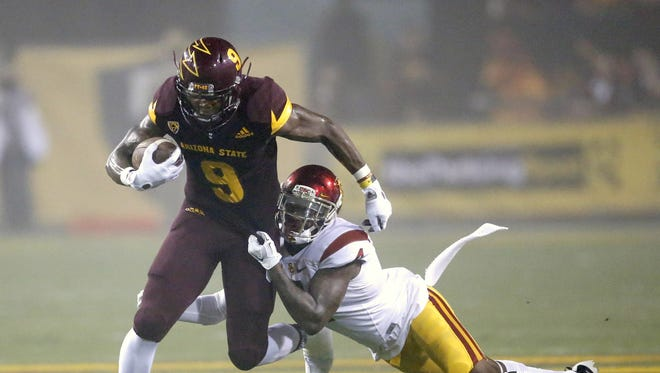 Arizona State University running back Kalen Ballage is tackled by USC safety Chris Hawkins during the first quarter of a college football game at Sun Devil Stadium in Tempe on Saturday, Sept. 26, 2015.