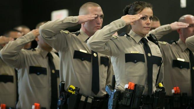 Cadet Melissa Agullo salutes the colors on Thursday, Feb. 25, 2016, during DASO's 21st Law Enforcement Academy Graduation Ceremony at DACC auditorium.
