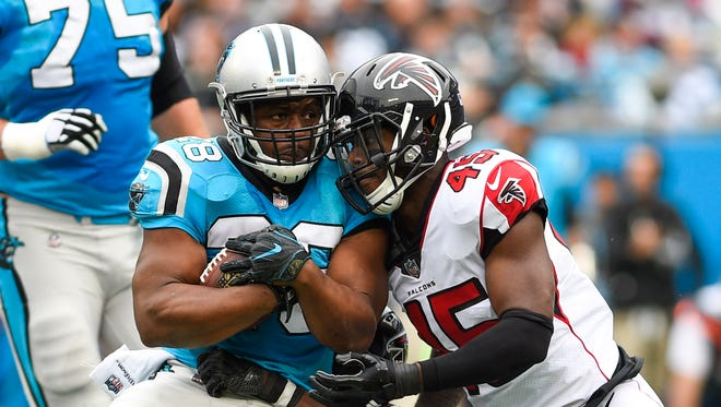 Carolina Panthers running back Jonathan Stewart (28) is tackled by Atlanta Falcons middle linebacker Deion Jones (45) at Bank of America Stadium.