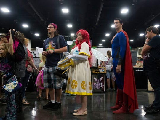 "From left center, Michael Stalcup of Bardstown, Ky., his fiance Pamela Spolsky, dressed as Aurora from ""Child of Light,"" and Lonnie Johnson of Perrysville, Mo., dressed as Superman, wait in line at the Fanboy Expo in the Knoxville Convention Center Saturday, June 24, 2017."