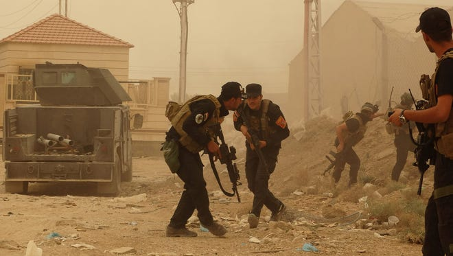 Iraqi security forces defend their headquarters against ISIL attacks in Ramadi last Thursday.