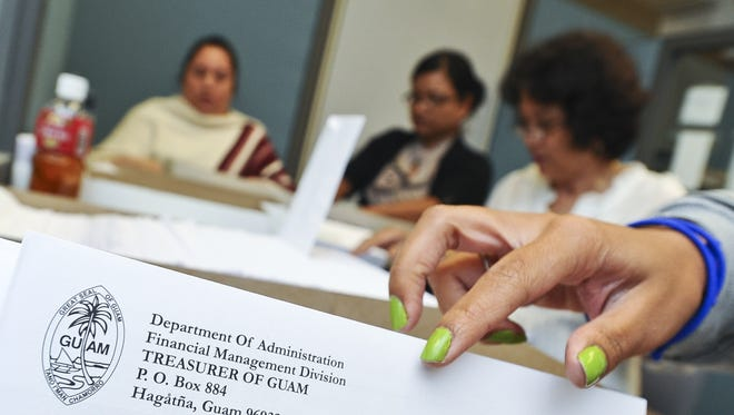 In this June 28, 2013, file photo, Department of Administration staff place tax refund checks into envelopes.