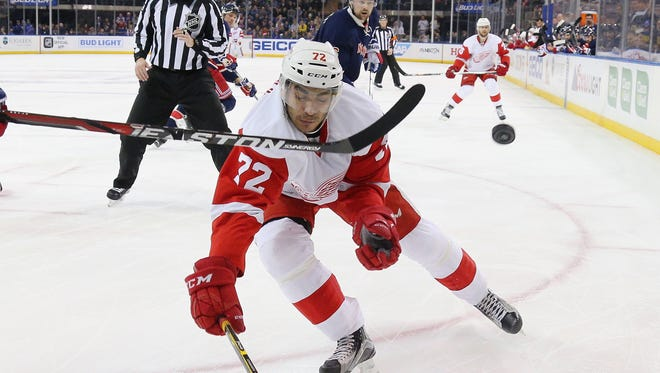 The Rangers' Dan Boyle shoots the puck away from Red Wings forward Andreas Athanasiou during the first period of Sunday's loss in New York.