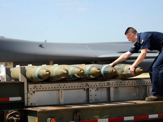 Senior Airman Calib Burkholder prepares bombs to be