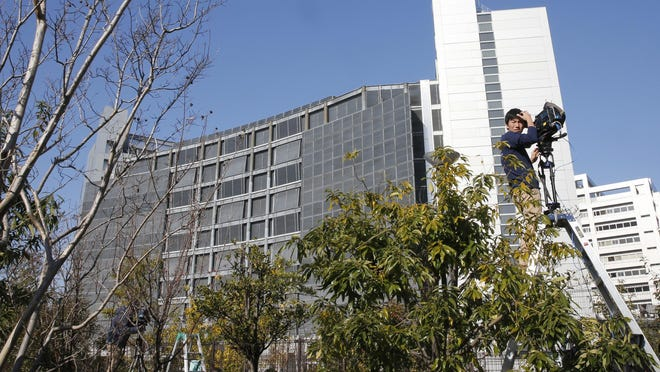 A cameraman on a ladder stands by outside Tokyo Detention Center, where former Nissan chairman Carlos Ghosn and former another executive Greg Kelly are being detained, in Tokyo.