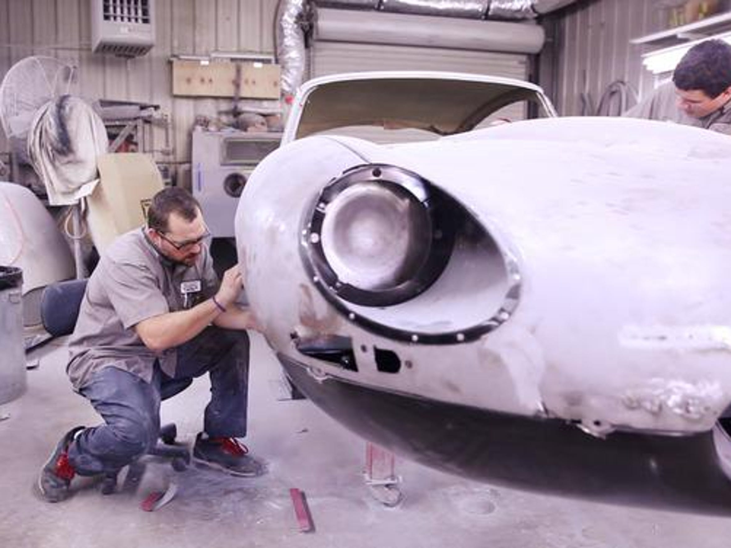 Auto body technicians Johnny Simonetti, left, of Staunton, and Andrew Vest, of Greenville, work on restoring a 1967 Jaguar XKE at Gassman Automotive Products in Waynesboro on Monday, Sept. 14, 2015.