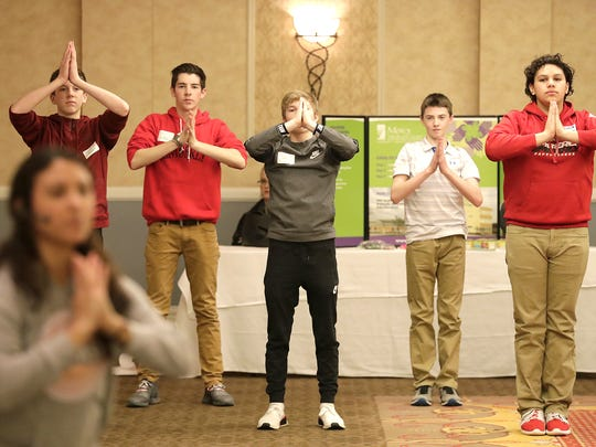 Students take part in a Yoga tutorial during the United Way Fox Cities' Teen Symposium on Monday, February 12, 2018, at the Radisson Paper Valley Hotel in Appleton, Wis.