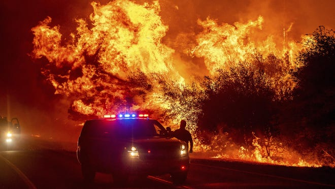 Flames lick above vehicles on Highway 162 as the Bear Fire burns in Oroville, Calif., on Wednesday. The blaze, part of the lightning-sparked North Complex, expanded at a critical rate of spread as winds buffeted the region.