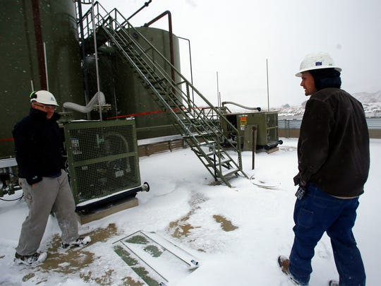 Jason Libersky, left, whose company is producing equipment to capture fugitive methane, and Cody Boyd, a field technician for WPX Energy, talk on Dec. 14 near an oil and gas site in Lynbrook.