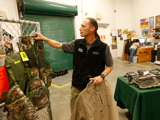 Nathan Asiu, store manager of the Farmington  Sportsman's Warehouse, talks on Wednesday about hunting apparel the store will feature at the Four Corners Outdoor and Travel Expo this weekend at McGee Park in Farmington.