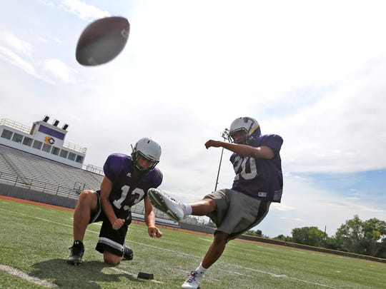 Derek Curley attempts a field goal with the help of quarterback Bryson Dowdy on Monday at Bronco Stadium in Kirtland.