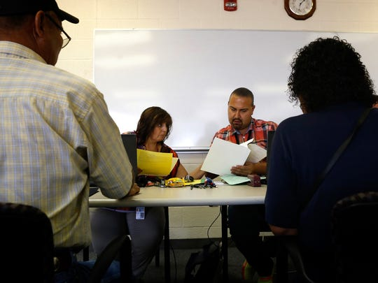 State of New Mexico Registrar Renee Valencia and State of New Mexico Quality Assurance Coordinator George Dominguez look over paperwork for birth certificates for Thomas Dobey, left, and Bessie Paul, right, on Thursday at the Northern Navajo Agency Nataani Nez Complex in Shiprock.
