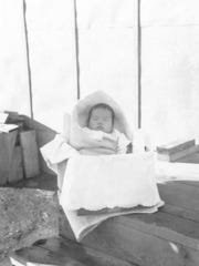 A 100-day-old David Ojima sits wrapped up in the Minidoka War Relocation Center. David was born in a relocation center in Puyallup.