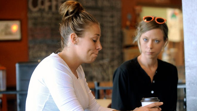 Brooke Beaton, 27, of Tea, S.D., left, talks about dealing with domestic violence in a Sioux Falls, S.D., coffee shop. Her friend, Tiffany Thoelke of Canton, S.D., photographed her when the bruises were a day old.