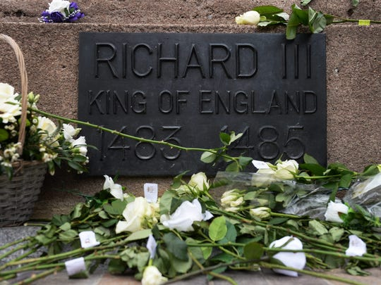 White roses lie at the foot of King Richard III's statue as his remains lie in repose at Leicester Cathedral during the public viewing of his coffin on March 23, 2015. The City of Leicester is preparing for the reburial of King Richard III who died in Bosworth in 1485.