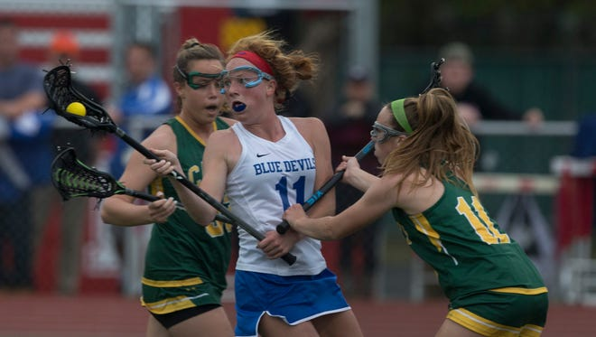 Shore's Mary Kate George looks to pass away as she gets heavy coverage working in towards goal. Shore Regional Girls Lacrosse vs Red Bank Catholic in Shore Conference Tournament Semifinals.