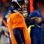 Denver Broncos quarterback Peyton Manning (18) watches the final seconds of an NFL divisional playoff football game against the Indianapolis Colts, Sunday, Jan. 11, 2015, in Denver. The Colts won 24-13 to advance to the AFC Championship game against the New England Patriots. (AP Photo/David Zalubowski)
