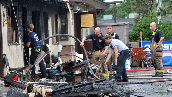 Fire crews on Monday pick through items destroyed in a fire at the Ponderosa Motel in Wausau.