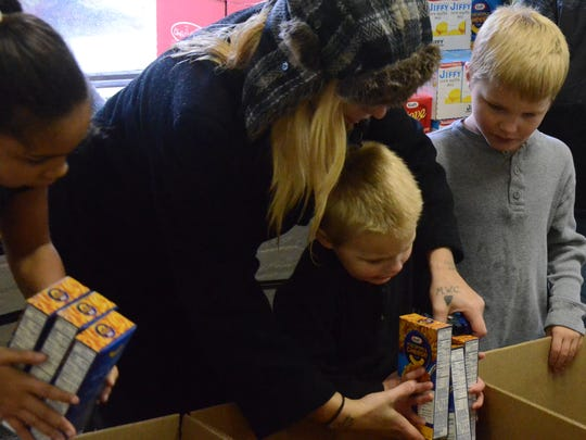 Mariah Leins helps her children, Marianna Leins-Moore, 8, from left, Christian Moore, 4, and Gabrielle Moore, 6, pack boxes.