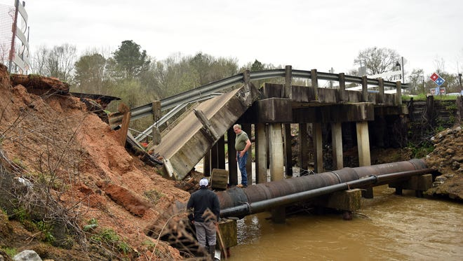 In this March 10 photo, Jackson employees inspect transmission lines for damage after a bridge collapsed on Robinson Road in Jackson.